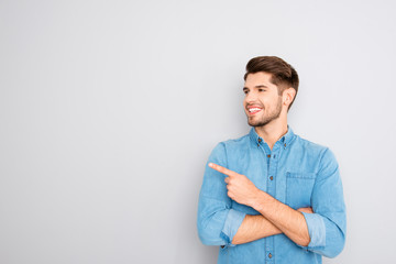 Cheerful young man pointing away on gray background Wall mural