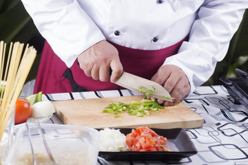 Chef chopping green bell pepper with knife before cooking