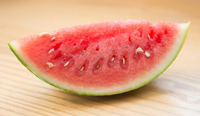 a piece of watermelon on a wooden table