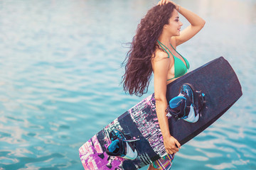 Young attractive woman with wakeboard Wall mural