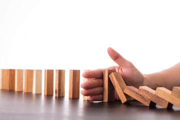 Stop domino risk effect ,businessman using hand for management s