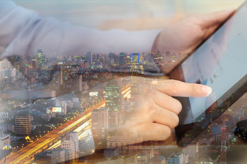 businessman hand on tablet with skyscraper background