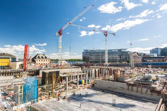 Großbaustelle mit Betonfundament und Kränen im Hintergrund