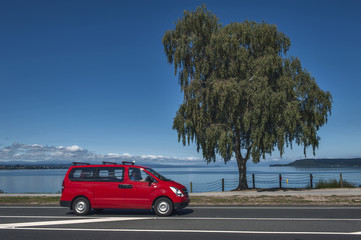 A red car driving along the coast of Lake Taupo in North Island of New Zealand