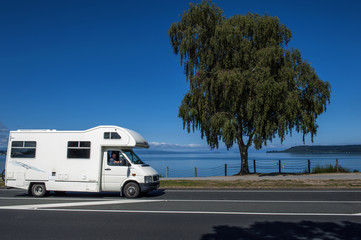 A motorhome driving along the coast of Lake Taupo in North Island of New Zealand