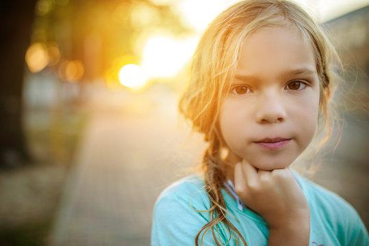Little girl on background of sunset on street