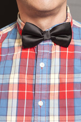 Man Dressed Checkered Shirt With Black Bow Tie On Gray