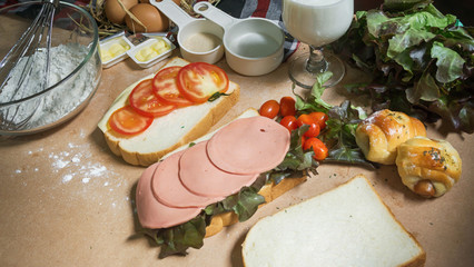 Preparing for big sandwich with ham, cheese and vegetables on wo