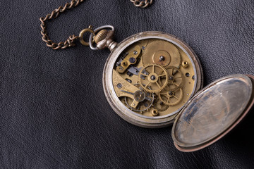 old clock mechanism on black leather background