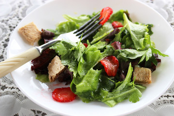 Green salad with strawberry pieces and a dressing of orange juic