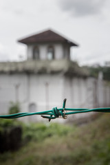 detail of barbed wire on the background of a prison guard tower