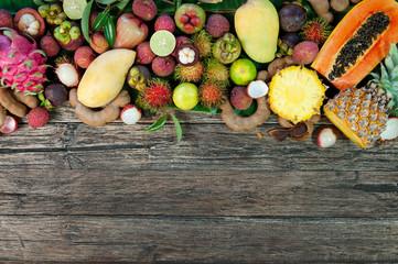 Poster Vruchten Fresh tropical fruit on wood on top
