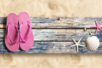 Summer beach accesories and marine life on old wooden boards on the sand beach