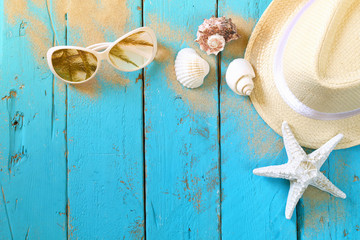 nautical concept with fedora hat, sunglasses and seashells