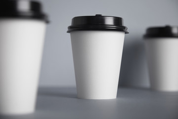 Three take away white paper cups with closed black caps, top view, isolated on simple gray background, central cup in close focus, cups aside are unfocused in bokeh