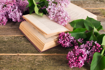 composition of the blooming lilac branches and open book on a wooden background shallow depth of field.
