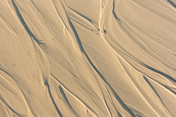 Pattern of sand after low tide at beach. Abstract Background.