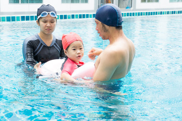 Family father mother and kid girl having fun In swimming pool