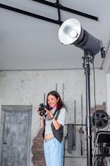 Photographer woman adjusts equipment flash, camera and softbox i