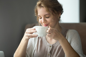 Half-length portrait of young beautiful female sitting at coffee shop with cup of tea or cappuccino. Woman enjoying hot drink in the morning. Attractive model sipping coffee with closed eyes