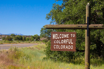 Welcome to Colorful Colorado sign next to a road in summertime