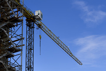 Construction site with crane on sky background. Low angle view.