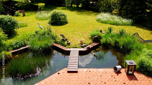 attraktiver naturbelassener garten mit an terrasse angrenzenden teich im fr hling stockfotos. Black Bedroom Furniture Sets. Home Design Ideas