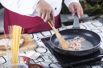 Chef frying bacon in the pan