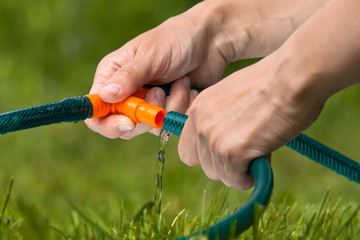 hands connecting hoses for irrigation of lawn or garden