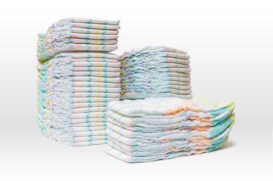 A lot of stacked diapers isolated on white background.