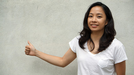Mixed race Asian girl thumb up with white concrete background