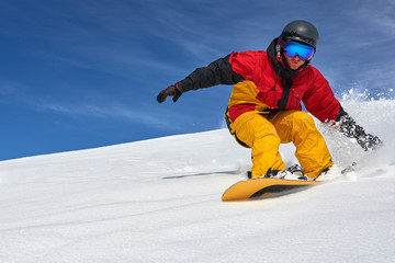 Snowboarder riding fast on dry snow freeride slope. Wall mural
