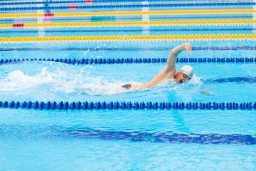 Man swimmer swimming crawl in blue water.