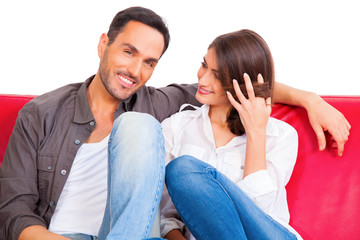 Smiling young man with girlfriend on sofa