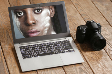 Dark-skinned woman portrait on laptop screen and digital camera. Close-up of laptop with beautiful dark-skinned girl and photo camera on wooden background.