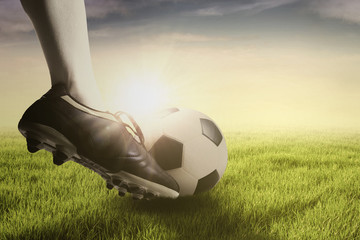 Foot doing free kick with ball at field