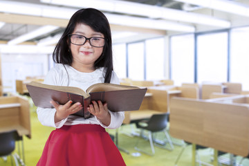 Little girl holds book in reading room
