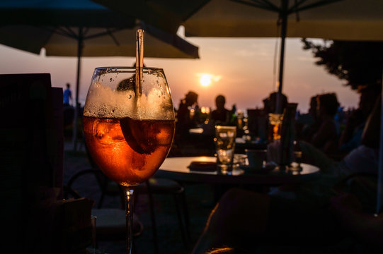 A glass of cold orange cocktail at the sunset on the table of a beach bar
