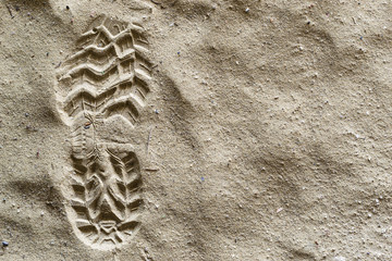 Close up bott or shoe print, left foot with grip set deeply into dirty sand, left side.