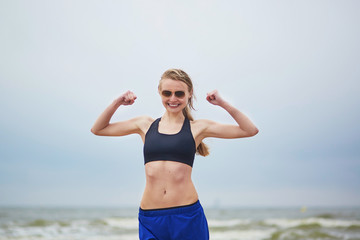 Young fitness running woman doing exercise on beach