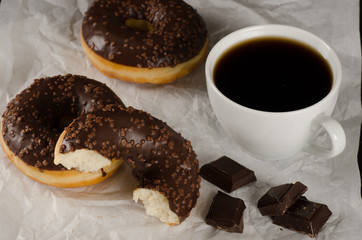 chocolate donuts with coffee and chocolate pieces on crumbled ba