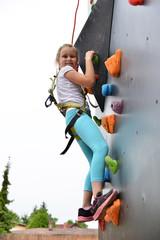 Youngster l'effort en escaladant un mur pour atteindre le sommet