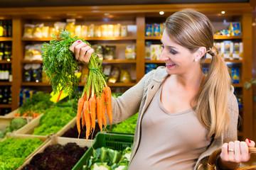 Schwangere Frau kauft gesundes Gemüse im Laden