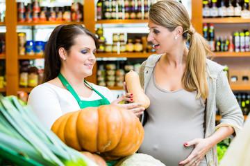 Frau kauft Kürbis und Gemüse beim Gemüsehändler