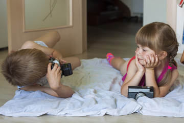 Little boy taking a picture of a little girl