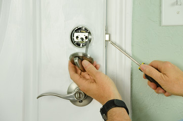 Closeup of a professional locksmith is installing or repairing a new deadbolt lock on a house exterior door with the inside internal parts of the lock visible