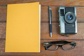 Overview wooden desk of creative,designer with notebook,glasses,pen and camera