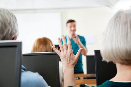 Senior Woman Raising Hand In Computer Class