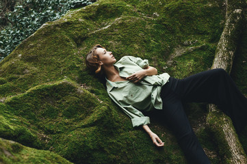 Pretty blonde posing on moss dressed in masculine shirt and stylish trousers.