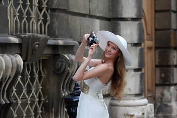 Fashionable young woman in white dress with a vintage camera